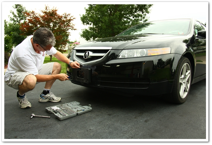 Removing the front license plate on an Acura TL prior to washing.