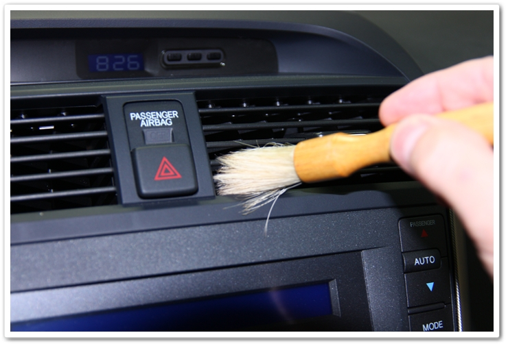 Cleaning tight areas of an interior of a 2006 Acura TL with a soft bristle brush