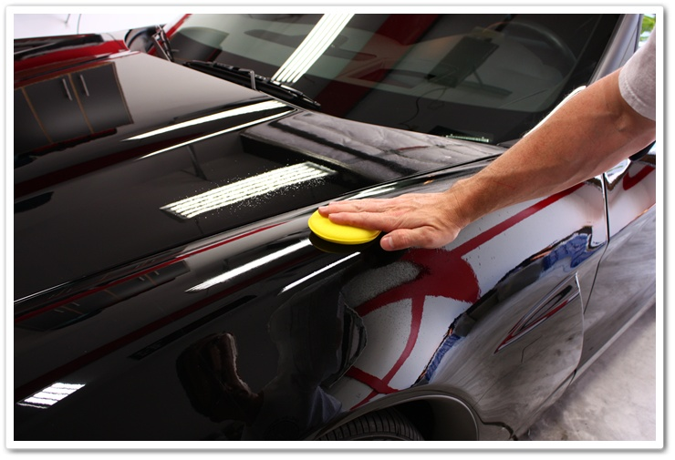 Optimum Opti-Seal being spread on to the paint of a black Corvette