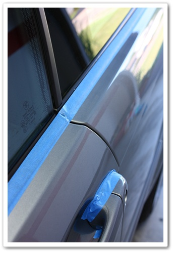 Taped up window trim and door handle on a BMW M3